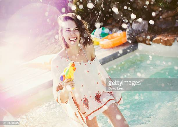 woman playing with water gun at pool party - pool party stock pictures, royalty-free photos & images