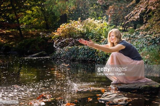 woman playing with waterand have fun on fresh air sitting near the lake in autumn city park - lena spoof stock pictures, royalty-free photos & images