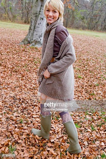 woman playing within heaps of dry leaves - gummistiefel frau stock-fotos und bilder