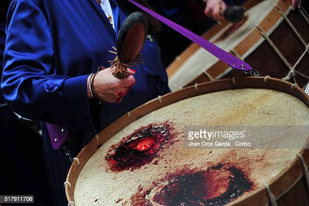 A woman plays a drum with bloodied and injured hands during Holy Week celebrations on March 25 2016 in Calanda Spain