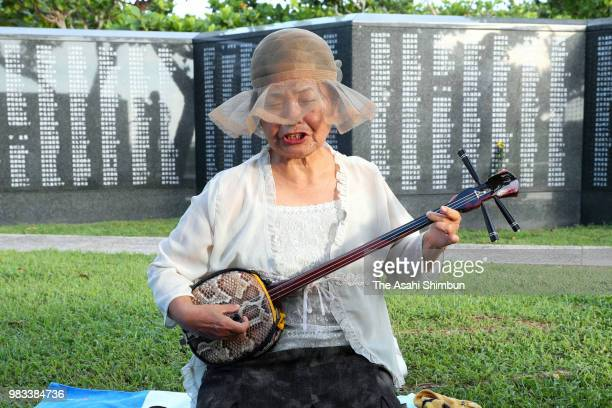 A woman plays a Sanshin at the Cornerstone of Peace where the names of their bereaved family members and relatives engraved at the Peace Memorial...