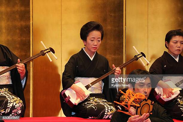 A woman plays a shamisen during a performance of the Nagauta Samonkai at Uchisaiwaicho Hall in Tokyo on Dec 16 2016 The threestringed instrument is...