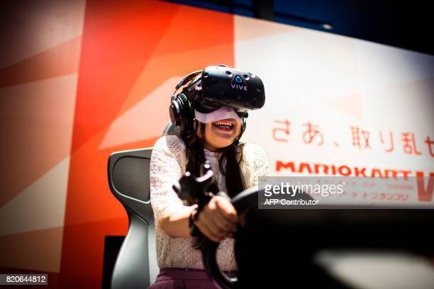 A woman plays a virtual reality Mario Kart game at the Bandai Namco game facility of VR Zone Shinjuku in Tokyo on July 22 2017 / AFP PHOTO / Behrouz...