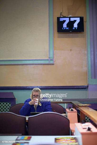 A woman plays Bingo at Carlton Bingo Hall in Orrell Park as the Chancellor George Osborne announces tax breaks for Bingo halls on March 19 2014 in...