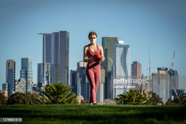 A woman plays football in the afternoon sun at Princes Park in Carlton on September 27 2020 in Melbourne Australia Victoria has recorded 16 new...