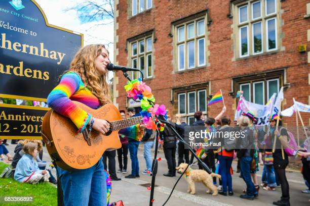 woman plays guitar as pride parade passes in exeter - istock stock pictures, royalty-free photos & images
