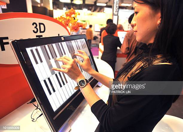 A woman plays music on a flat panel screen using multipletouch technologies at a booth of the Taipei World Trade Centre where Computex Taipei Asia's...