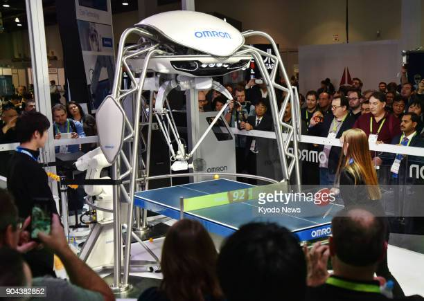 A woman plays table tennis with a robot developed by Omron Corp at a consumer electronics show or CES in Las Vegas on Jan 11 2018 ==Kyodo