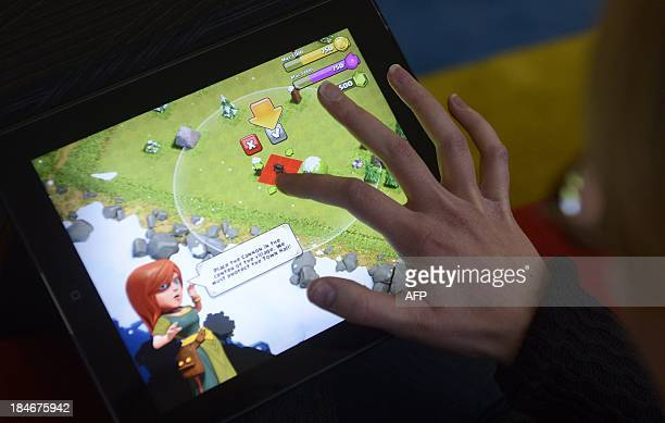 A woman plays the Clash of Clans game of Finnish computer game maker Supercell on a tablet computer on December 14 2012 in Helsinki Finnish computer...