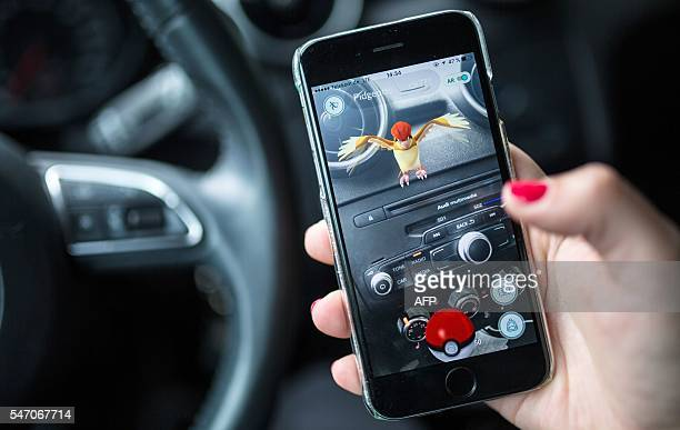 A woman plays the Pokemon Go mobile game on her smart phone in a car in Berlin on July 13 2016 The Pokemon Go mobile gaming craze reached European...