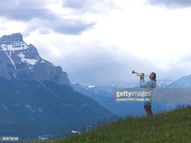 woman plays trumpet on mountain hillside - トランペット ストックフォトと画像