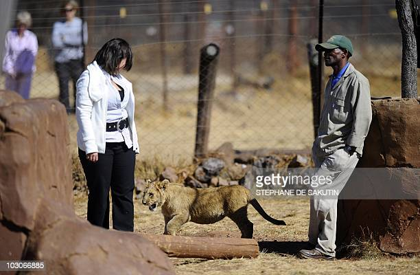 A woman plays with a lion cub at the orphenage of the private Rhino and Lion Nature Reserve on July 21 2010 in Krugersdorp north of Johannesburg AFP...