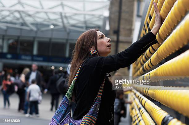 CONTENT] A woman plays with a temporary sound installation outside new entrance to Kings Cross Station London