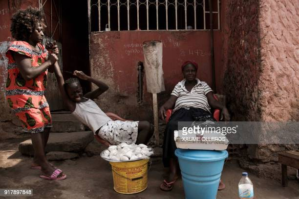 A woman plays with her daughter as they sell goods in the Mindara neighbourhood in Bissau on Mardi Gras on February 13 2018 / AFP PHOTO / Xaume...