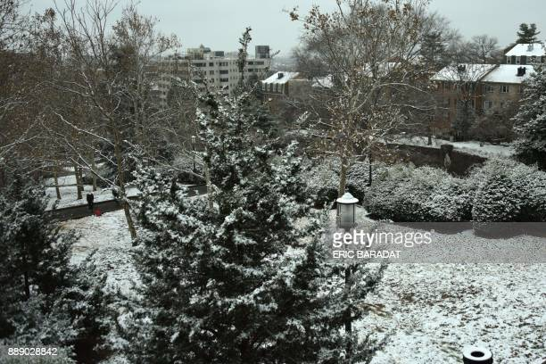 A woman plays with her dog as snow falls on Meridian Hill Park in Washington DC on December 9 2017 A rare early winter snowstorm hitting the...