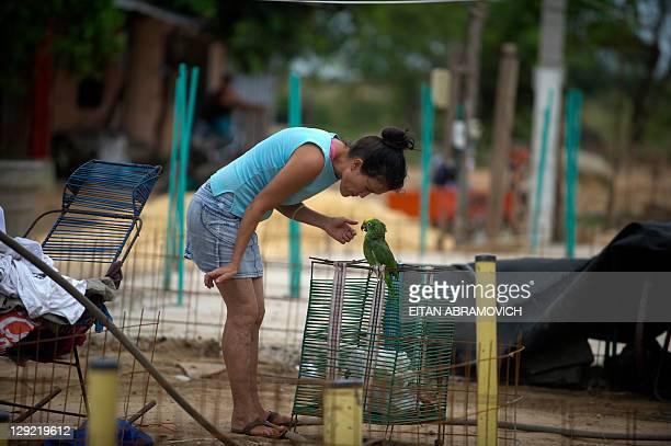 A woman plays with her parrot outside her house in Puerto Gaitan Meta department eastern Colombia on October 9 2011 The oil bonanza that goes through...