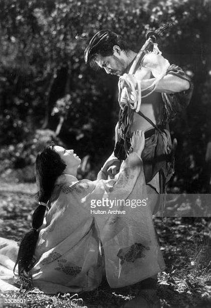 A woman pleading with a bandit in a scene from the Akira Kurosawa film 'Rashomon' set in 12th century Kyoto The film offers four different versions...