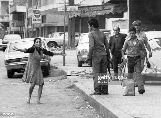 A woman pleads for help for her wounded husband in the Dekwan district of Beirut during street fighting in the civil war in Lebanon