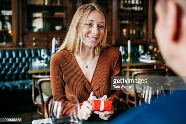 woman pleased after receiving gift from partner in restaurant - receiving stock pictures, royalty-free photos & images