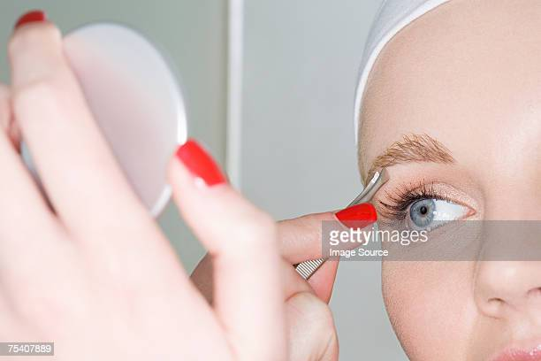 Woman plucking eyebrow