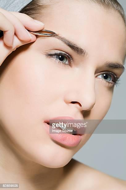 woman plucking eyebrow - 修眉 個照片及圖片檔