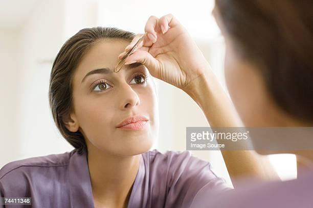 woman plucking eyebrows - 修眉 個照片及圖片檔