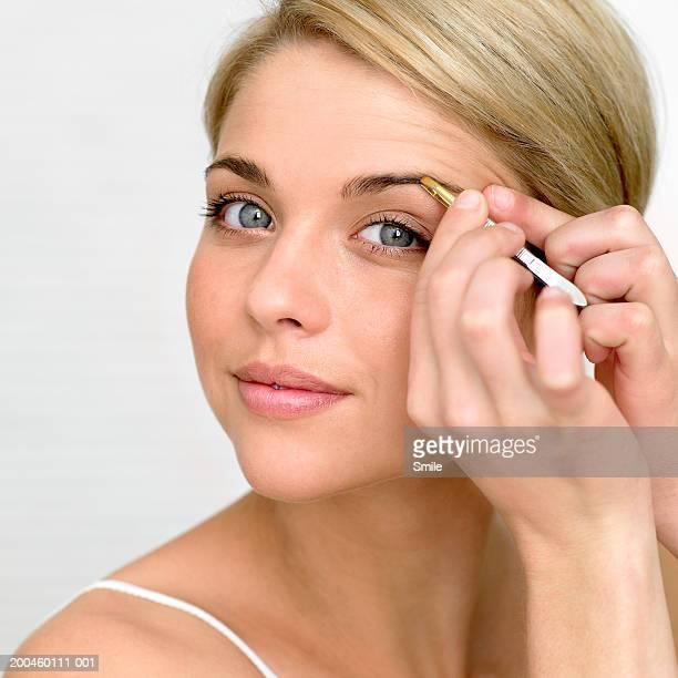woman plucking eyebrows, portriat - 修眉 個照片及圖片檔