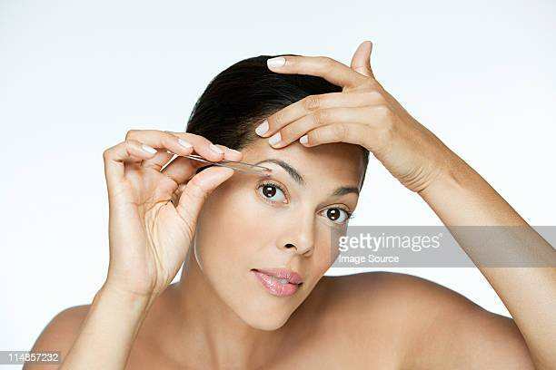 Woman plucking her eyebrows