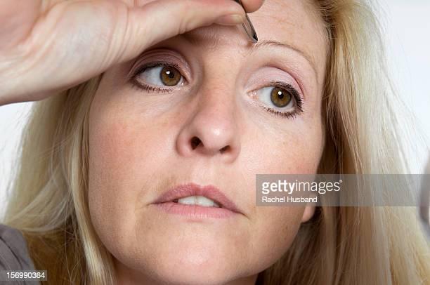 a woman plucking her eyebrows - 修眉 個照片及圖片檔
