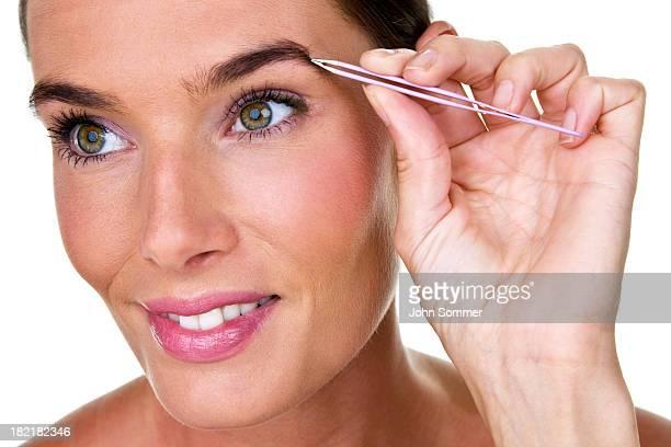 woman plucking her eyebrows - 修眉 個照片及圖片檔
