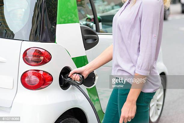 Woman plugging in Smart electric drive car in city