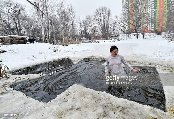 TOPSHOT A woman plunges into a crossshaped hole in Kiev on January 19 as part of Orthodox Epiphany celebrations Nearly two million Russians bathed in...