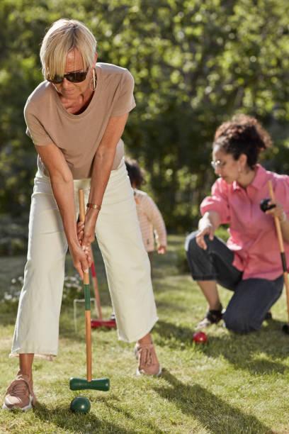 Woman plying croquet in garden