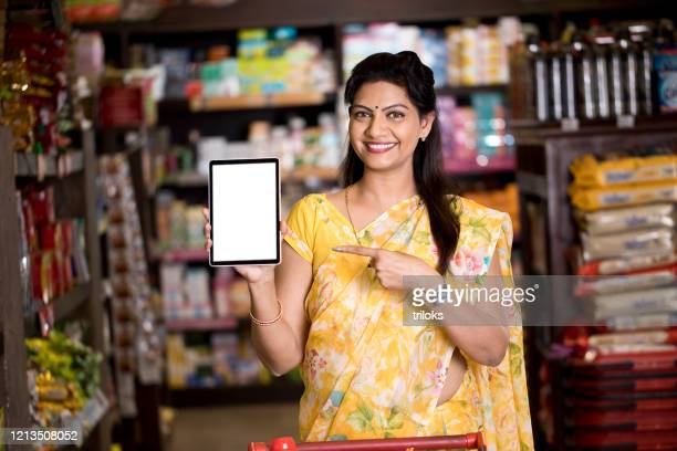 woman pointing at blank digital tablet screen in supermarket - indian culture stock pictures, royalty-free photos & images