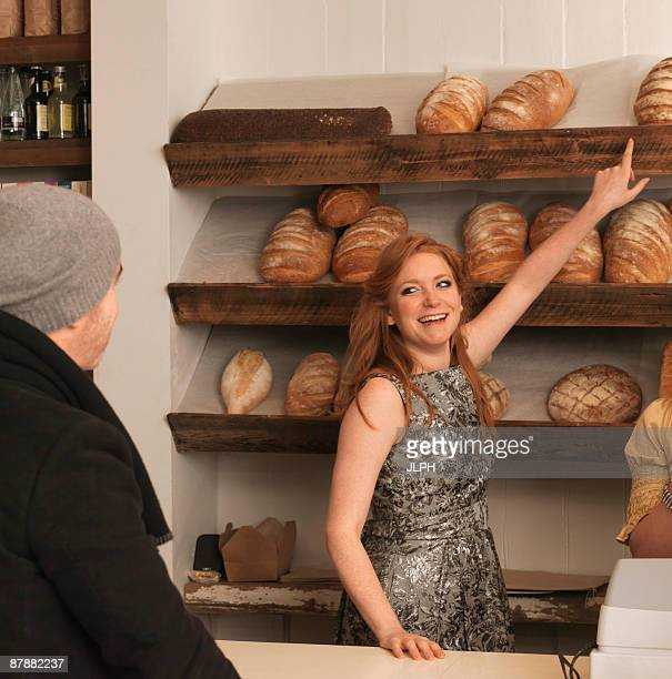 Woman pointing at bread on shelf