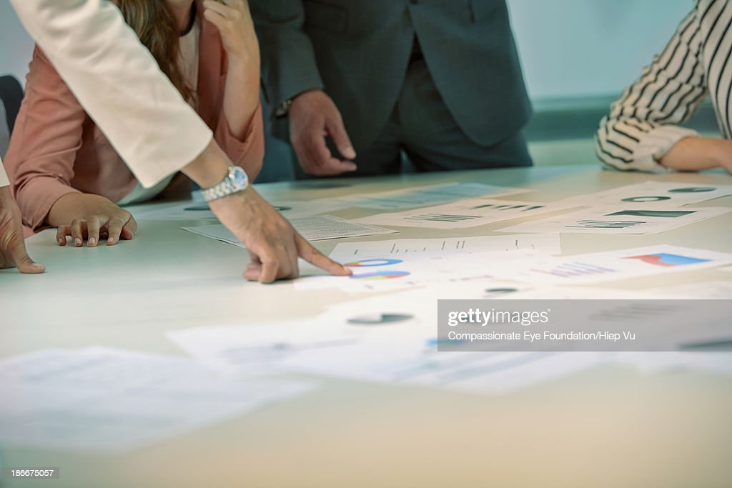 Woman pointing at document on table in meeting : Bildbanksbilder
