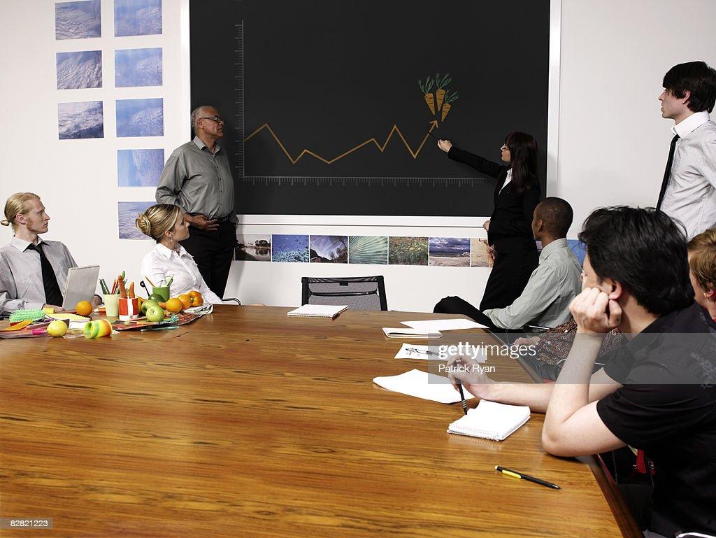 Mulher a apontar com gráfico de crescimento de Cenouras : Foto de stock