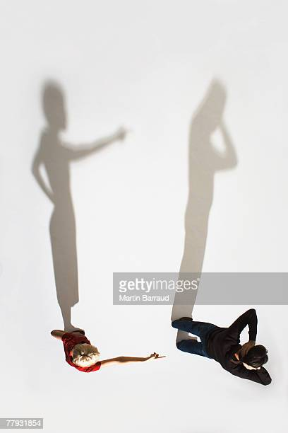 Woman pointing at man facing away from her