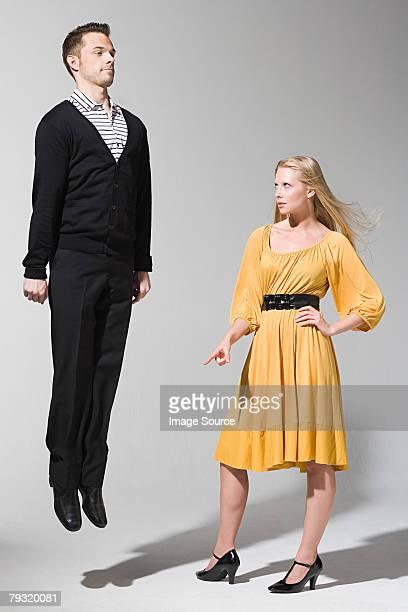 A woman pointing at man jumping