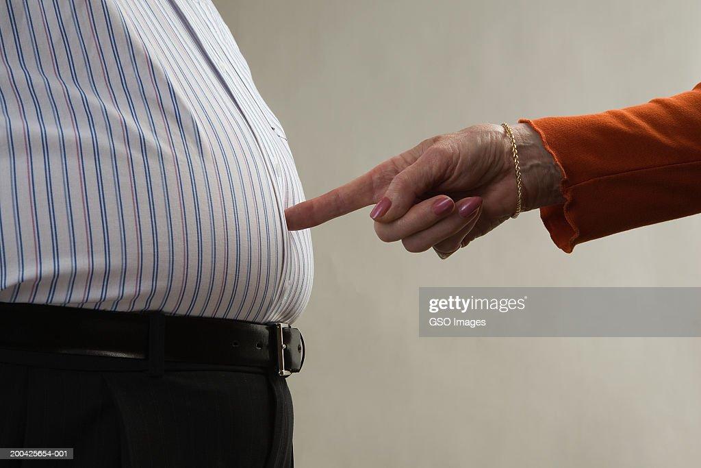 Woman pointing at senior man's stomach, close-up : ストックフォト