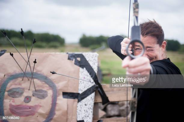 Woman pointing bow at viewer