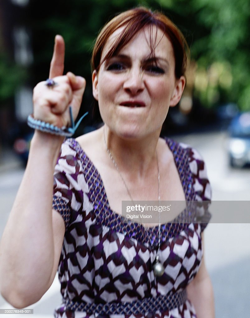 Woman pointing finger aggressively, portrait : Stock Photo