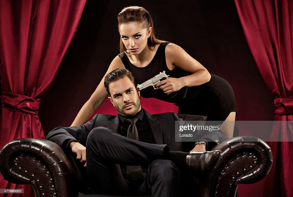 woman pointing gun to man sitting on chair : Stock Photo