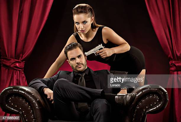 woman pointing gun to man sitting on chair - women dominating men stock photos and pictures