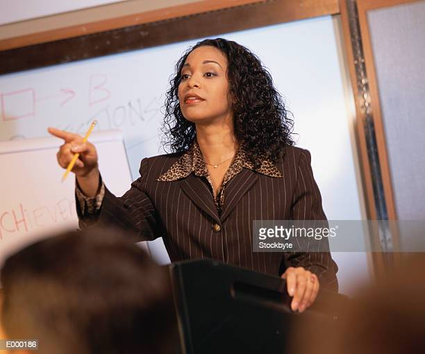 Woman pointing, standing in front of whiteboard