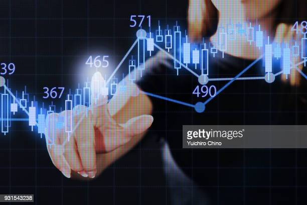 woman pointing the stock market graph with virtual screen - hud graphical user interface stock photos and pictures