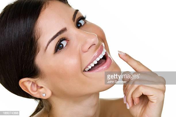 donna che punta alla sua perfetto sorriso - sorriso aperto foto e immagini stock