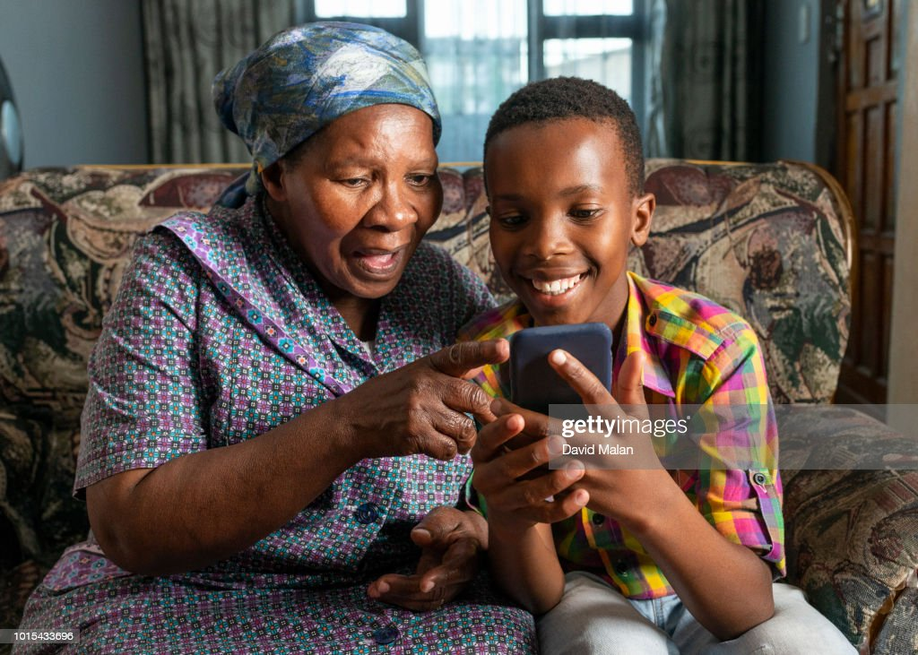 Woman pointing to something on her grandson's mobile phone. : Stock Photo