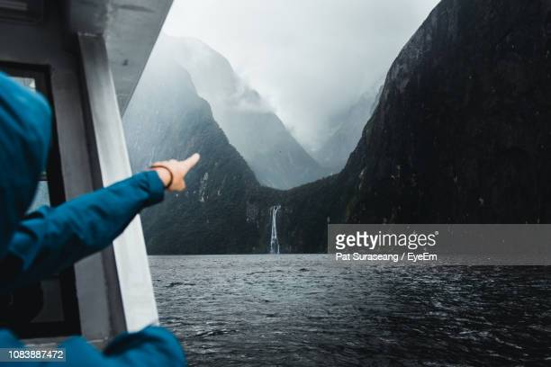 woman pointing towards waterfall and mountains - south island new zealand stock pictures, royalty-free photos & images