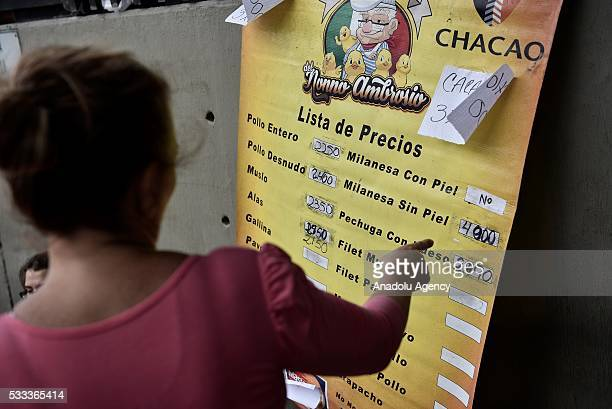 A woman points out to a price list of chicken filet w/o skin of 4000 bolivars per kilo equivalent to 63492 US dollars at the official exchange rate...
